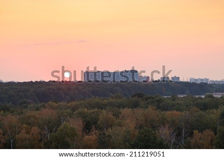 sun above horizon during red sunrise over houses and urban park in summer morning - stock photo