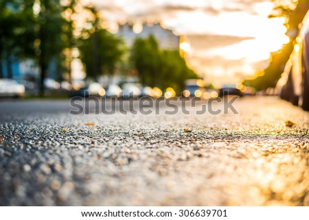 Sun after the rain in the city, headlights of the approaching cars, view from the road level - stock photo
