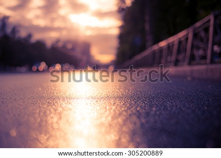 Sun after the rain in the city, the lights of the approaching car, the view from the road level. Image in the soft orange-purple toning - stock photo