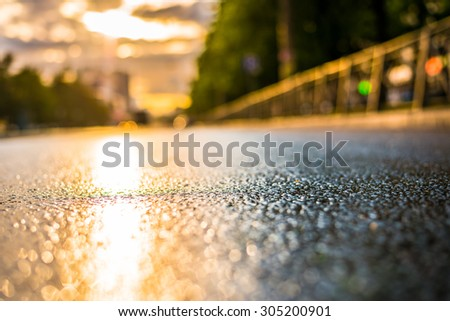 Sun after the rain in the city, view from the road level - stock photo