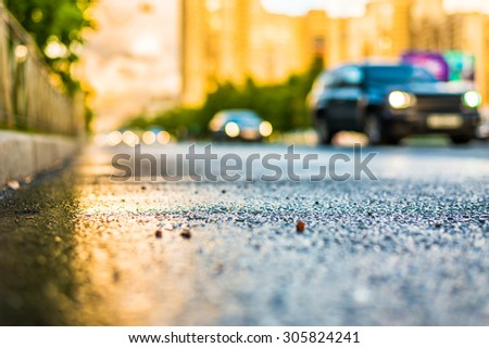 Sun after the rain in the city, view of the approaching cars with a level of puddles on the pavement - stock photo