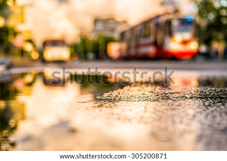 Sun after the rain in the city, view of the approaching tram with a level of puddles on the pavement - stock photo