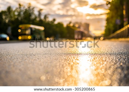 Sun after the rain in the city, view of the bus with a level of puddles on the pavement - stock photo