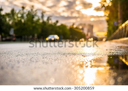 Sun after the rain in the city, view of the car with a level of puddles on the pavement - stock photo