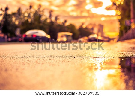 Sun after the rain in the city, view of the cars with a level of puddles on the pavement. Image in the yellow-purple toning - stock photo