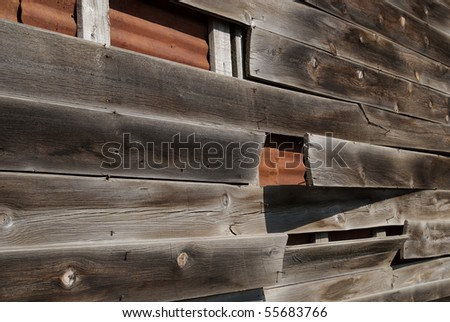 Sun-aged wood siding peels back from a shed in the Oregon desert