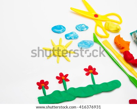 Sun and clouds and flowers made from plasticine - stock photo
