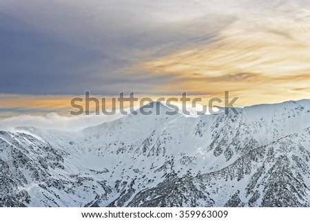 Sun and clouds atop of Kasprowy Wierch of Zakopane on Tatras in winter. Zakopane is a town in Poland in Tatra Mountains. Kasprowy Wierch is a mount in Zakopane and the most popular ski area in Poland - stock photo
