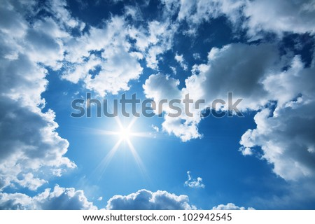 Sun and clouds in a blue sky - stock photo