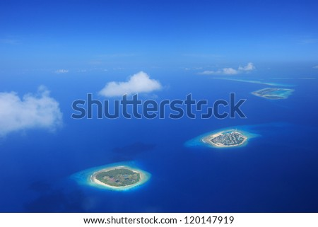 Sun and clouds over islands in Laccadives sea, Maldives, shot with a tilt and shift lens - stock photo