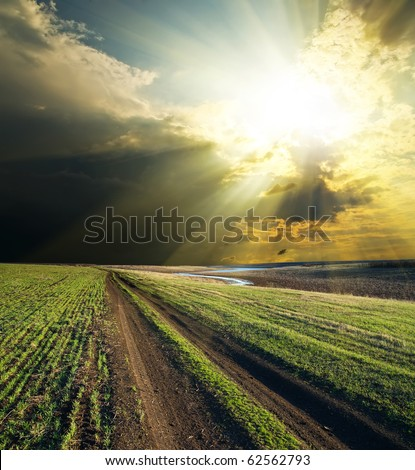 sun and clouds over road - stock photo
