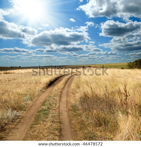 sun and clouds over rural road - stock photo