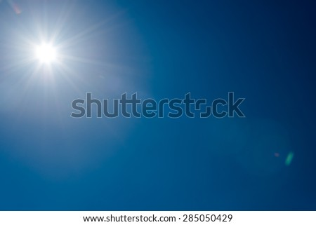 Sun and flare  in clear blue sky without clouds - stock photo