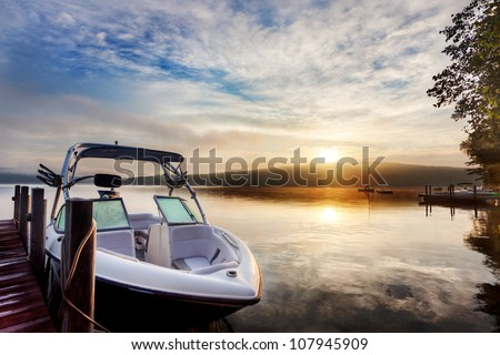 Sun and mist on a Summer New Hampshire boat dock at sunrise - stock photo