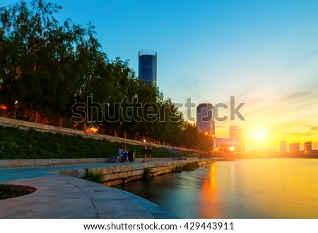 sun and the beautiful sunset over the city center and city pond of Yekaterinburg in summer - stock photo