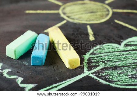 Sun and tree drawing and chalks on a blackboard - stock photo