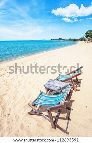 sun beach chair on shore near sea. Thailand - stock photo