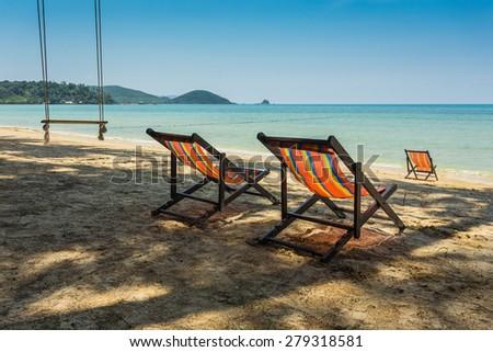 sun beach chairs on shore near sea. Thailand - stock photo