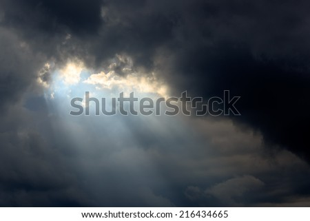 Sun beam in Dark Clouds and Sky before Thunderstorm - stock photo
