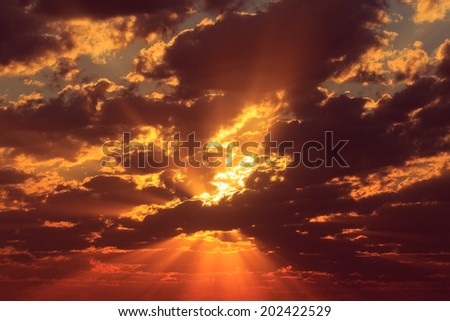 Sun beams at sunrise make way through clouds and shine fiery color