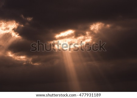 Sun beams shining through gloomy clouds