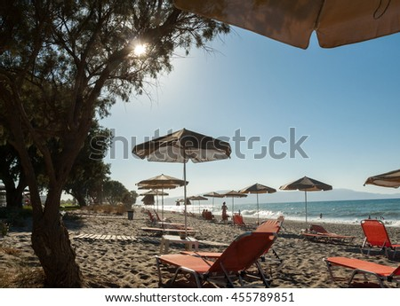 Sun beds and shade umbrellas  at a beach on Crete. Greece - stock photo