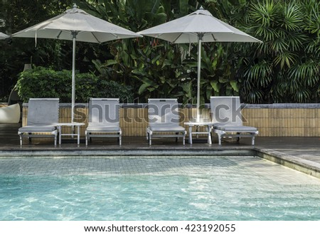 Sun beds and umbrellas at the poolside. Thailand