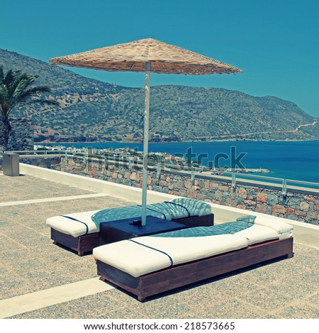 Sun beds and umbrellas on terrace in a luxury summer resort with Mediterranean sea view (Crete, Greece). Square image, Instagram effect - stock photo