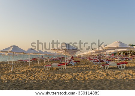 Sun beds and umbrellas on the beach in the morning. - stock photo