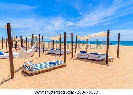 Sun beds on sandy beach in Salema seaside town, Alrgarve region, Portugal - stock photo