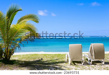 Sun beds on tropical white sand beach. Taken in Mauritius. - stock photo