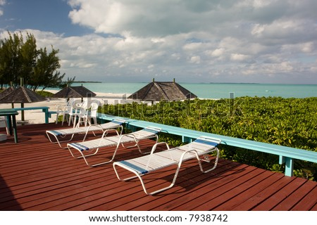 sun beds on wooden deck overlooking beach
