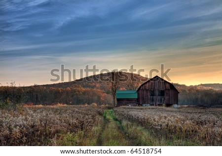 Sun begins to rise over a rustic old barn. - stock photo