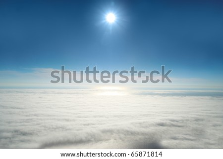 Sun, blue sky, and ocean of clouds - stock photo