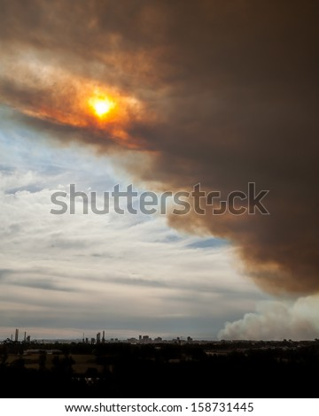 Sun breaking through bushfire smoke clouds over the Parramatta Skyline in Sydney, NSW, Australia - stock photo