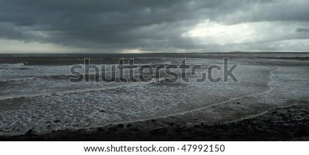 Sun breaking through clouds along the ocean shore - stock photo
