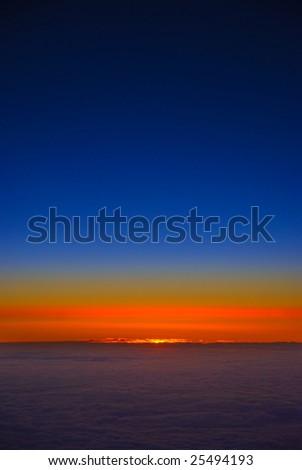 Sun breaking through cloudy horizon at dawn - stock photo