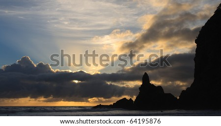 Sun bursting through the clouds on Piha coast, new zealand - stock photo