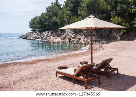 Sun chairs situated on the beach on the islands of Croatia. - stock photo