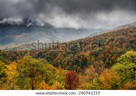 Sun clears the fog over a mountain ridge bursting with autumn color - stock photo