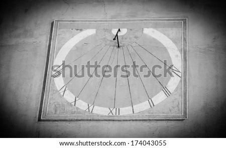 Sun clock on a wall of the City hall in the medieval town Entrevaux (Alpes de Haute Provence, France). Aged photo with shadowed angles. Black and white. - stock photo