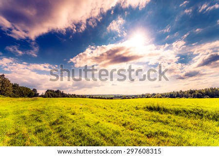 Sun comes out of cumulus clouds and illuminates a fields in the forest. Image in the orange-blue toning - stock photo