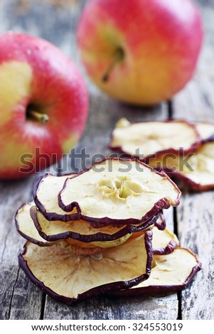 Sun dried apple chips on a rustic wooden table.Healthy snack.Selective focus - stock photo