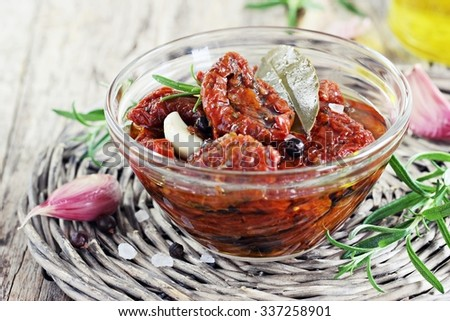 Sun dried tomatoes in olive oil on a rustic wooden table.Selective focus - stock photo