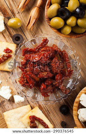 Sun dried tomatoes with cubes of feta cheese in olive wood bowl and green and black olives on rustic wooden background.  Selective focus. Top view. - stock photo