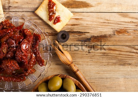 Sun dried tomatoes with cubes of feta cheese in olive wood bowl and green and black olives on rustic wooden background.  Selective focus. Top view. Copy space. - stock photo