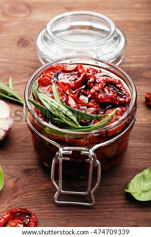 Sun dried tomatoes with rosemary and basil in a glass jar on a brown wooden surface. Traditional recipes of the Mediterranean cuisine. Vegetarian concept