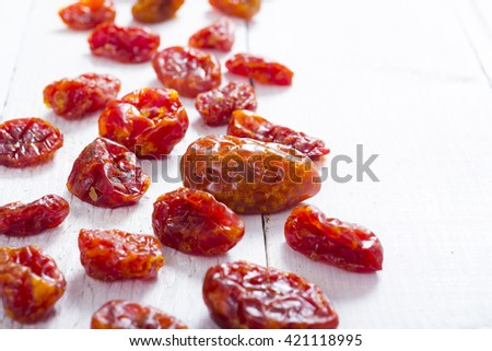 sun dried whole tomatoes on white wood table background