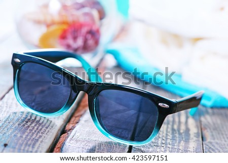 sun glasses and flip flops on wooden backgroubd