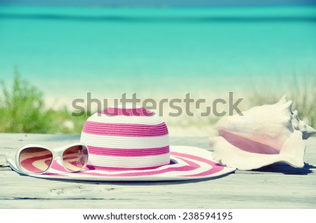 Sun glasses and hat against tropical beach of Great Exuma island, Bahamas - stock photo